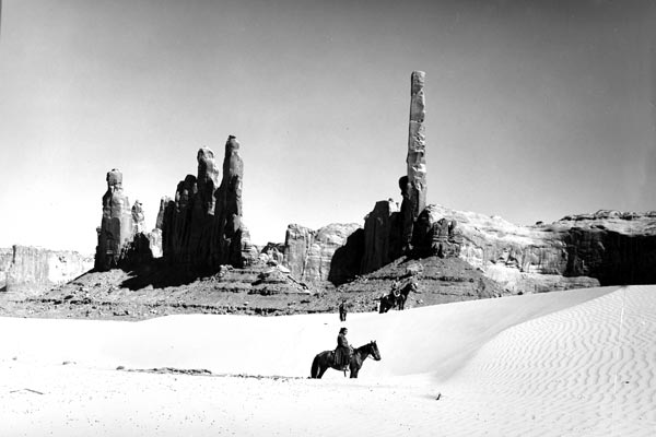 Black and white photo of Navajo on horseback